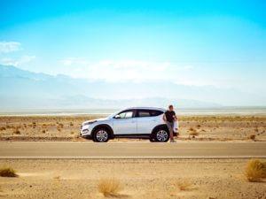 Homem jovem parado ao lado de seu carro branco em uma estrada por causa de sua bateria descarregada