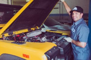 Homem jovem com vestes de mecânico mexendo com o motor de um veículo grande que está com a bateria descarregada