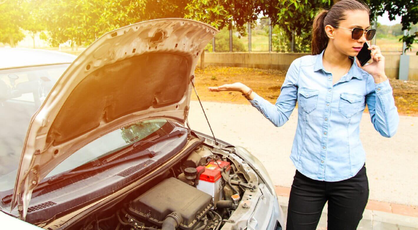 Mulher jovem falando ao telefone do lado de um carro com o capô aberto, aparentemente confusa com a sua bateria descarregada