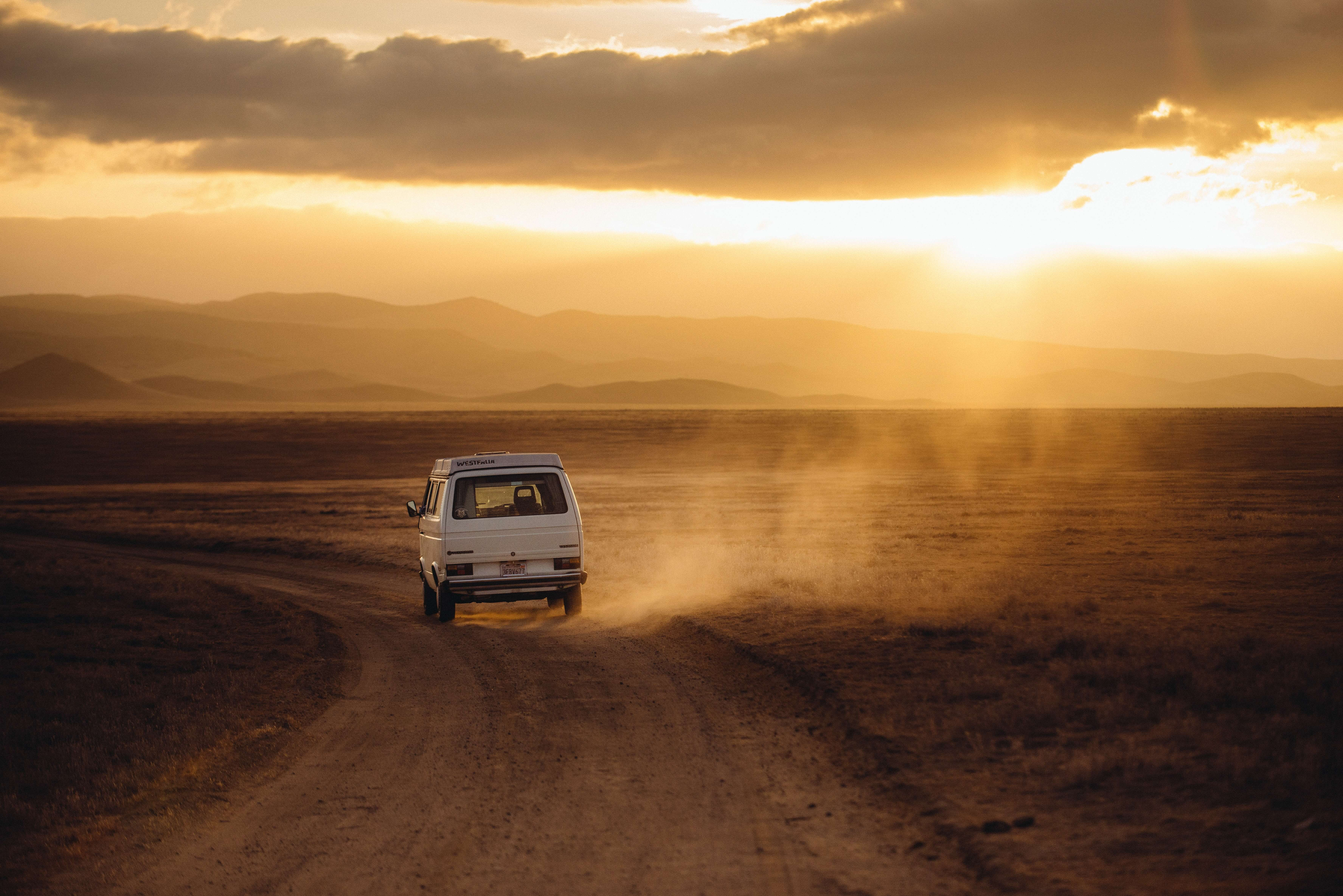 Um carro branco acelerando em uma estrada de terra, buscando onde comprar bateria