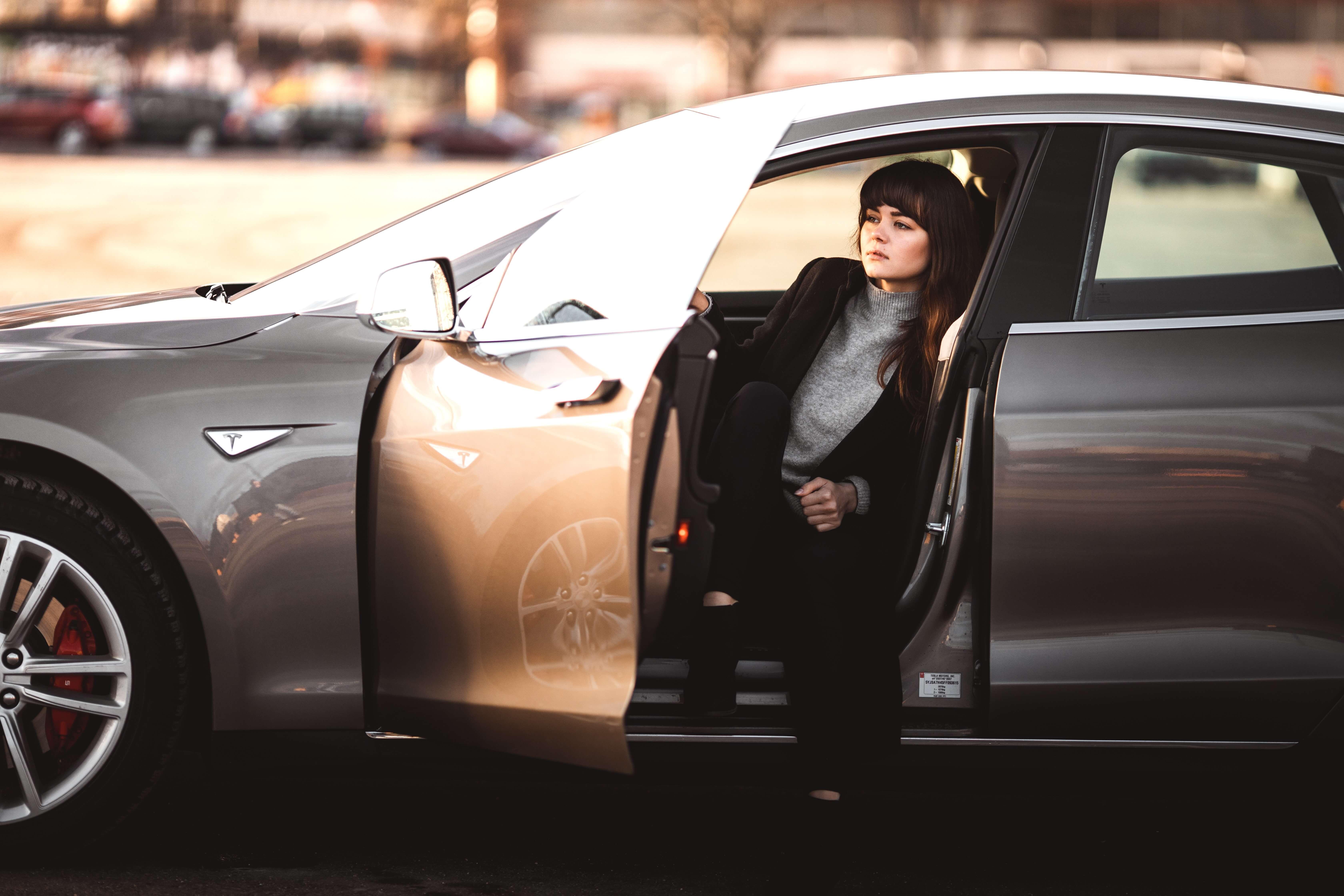 Mulher sentada no banco de motorista de um carro com a porta aberta, pensando sobre valor de bateria de carro