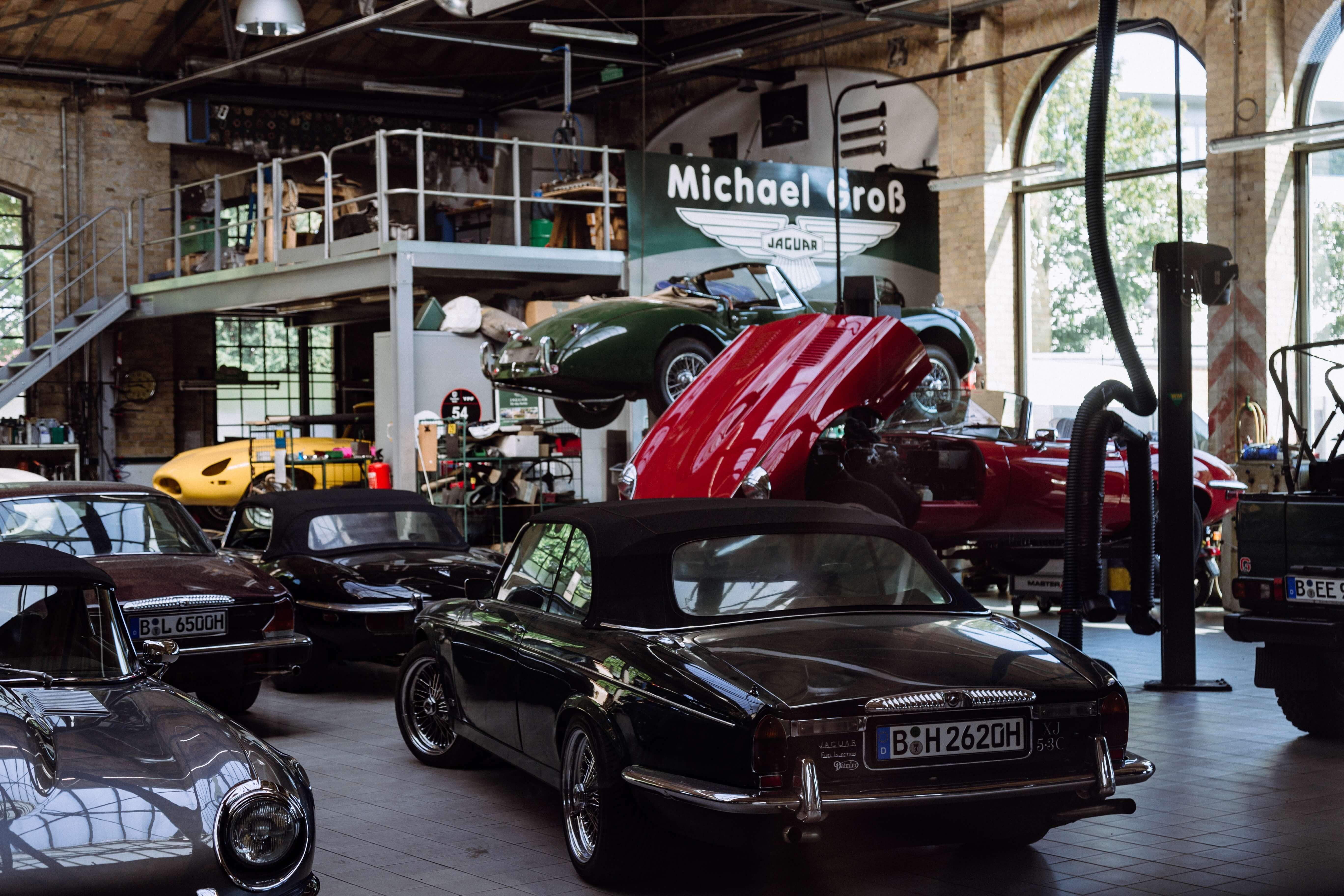 Vários carros em uma loja mecânica, onde é possível saber o preço de bateria de carro