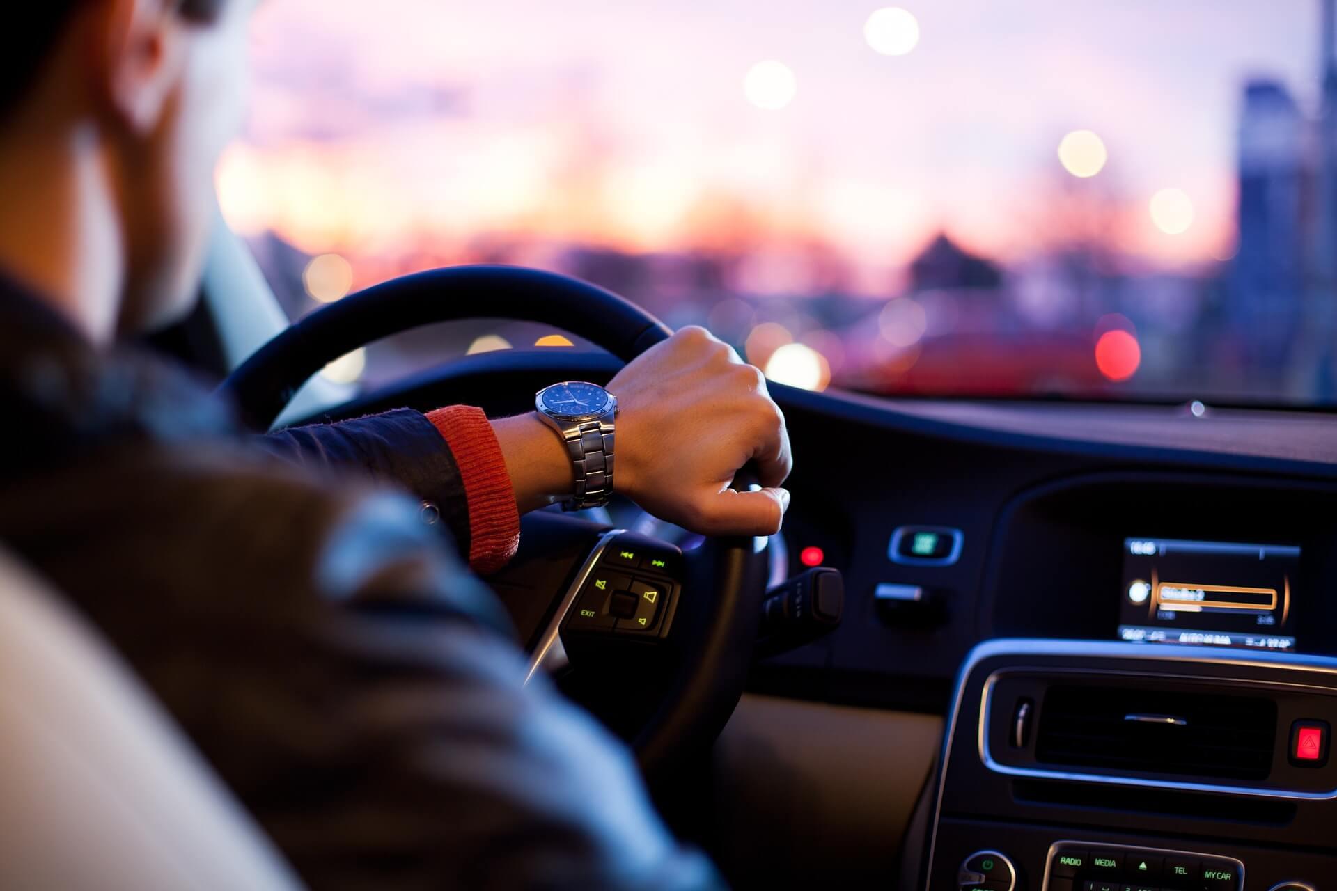Recorte de um braço com jaqueta de coura e relógio dirigindo um carro
