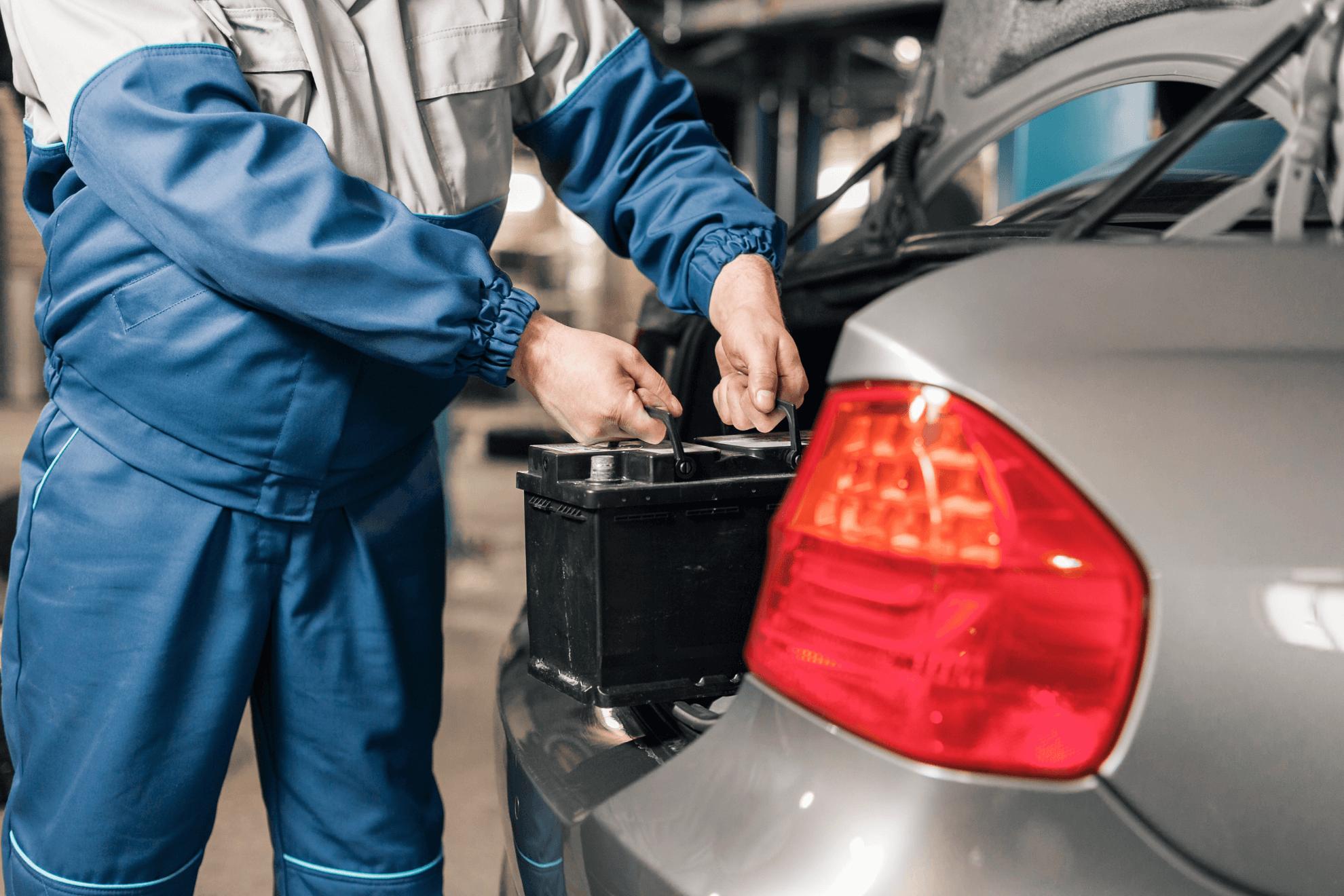 Homem com uniforme de mecânico colocando uma bateria nova em um carro