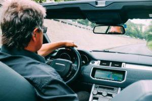 Homem de meia idade de costas dirigindo um carro