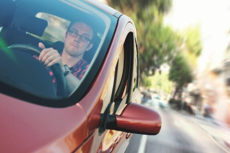 homem dirigindo para comprar bateria de carro