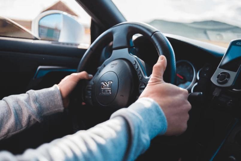 pessoa com as mãos no volante tentando ligar mas o carro não dá partida