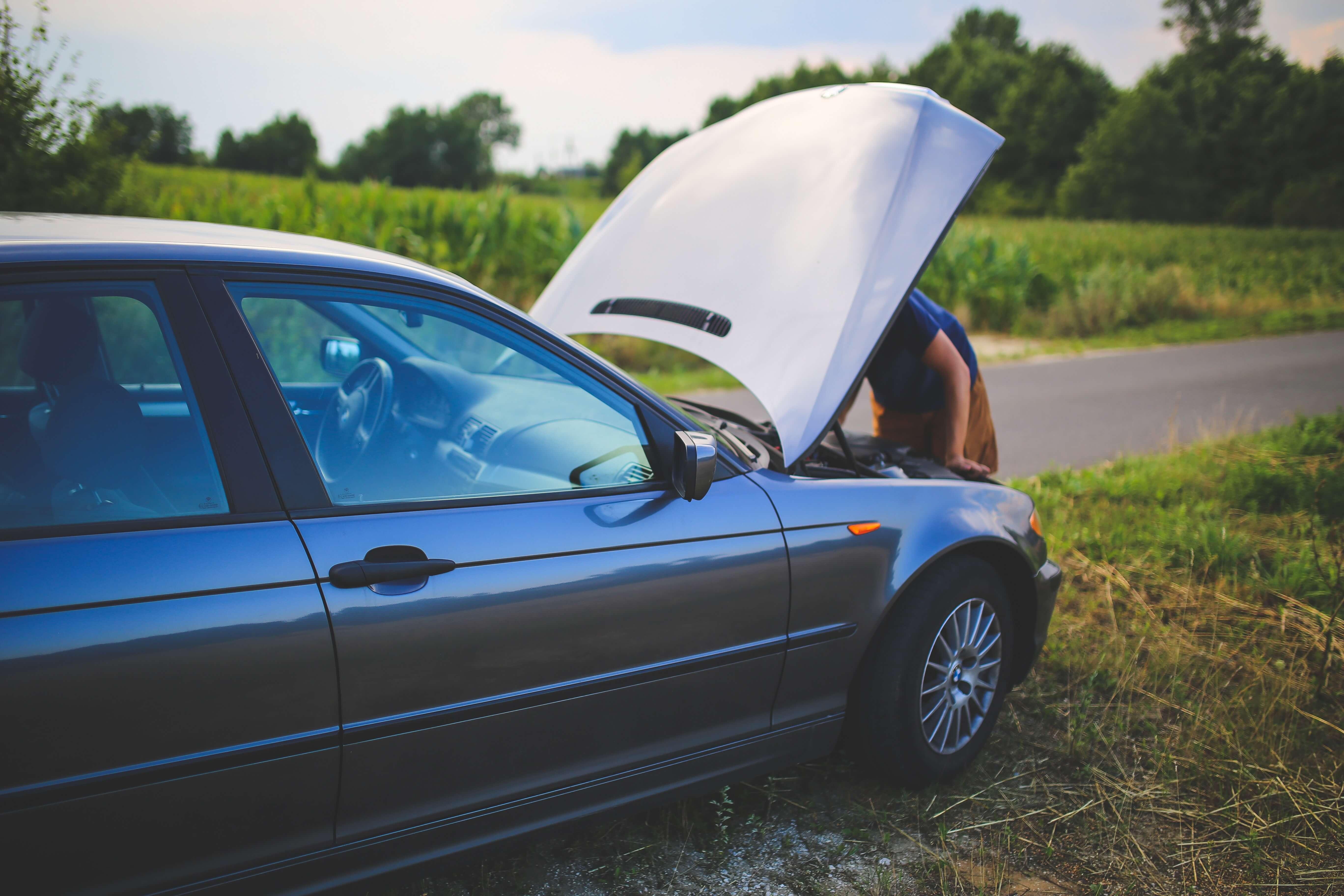 homem mexendo no motor e avaliando se vale a pena aprender como recuperar bateria de carro