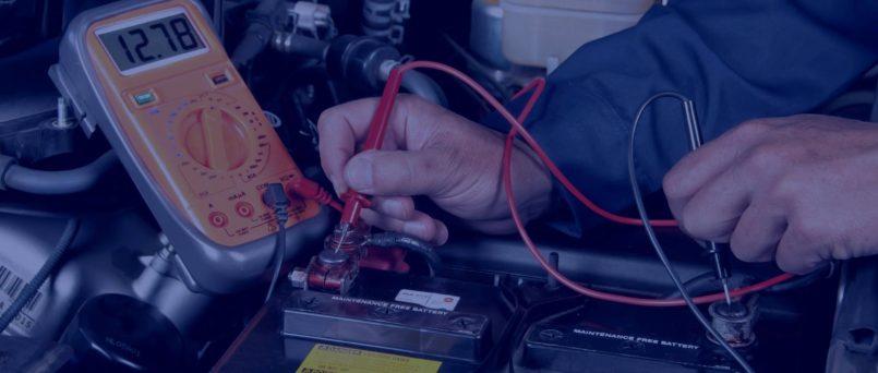 ateria de carro sendo testada por mãos masculinas e um aparelho próprio, para definir se precisa trocar bateria ou recarregar.